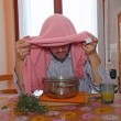 Man with pink towel breathe balsam vapors to treat colds — Stock Photo
