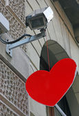 Red heart hanging from a surveillance camera of a bank — Stock Photo