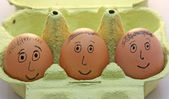Three eggs with smiling eyes and nose and mouth and hair — Stock Photo