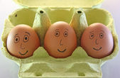 Three eggs with smiling eyes nose and mouth — Stock Photo
