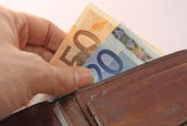 Hand that pays taking the euro money from wallet — Stock Photo