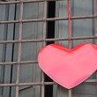 Red heart hanging on the grid of a window outside a building on — Stock Photo