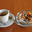Ashtray chock full of cigarette butts and a cup of espresso — Stock Photo