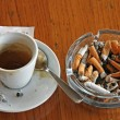 Cup of coffee espresso and ashtray chock full of cigarette butts - Stock Photo