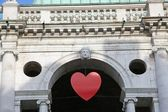 Red heart hanging at the Basilica Palladiana in the Piazza dei S — Stock Photo