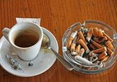 Cup of coffee espresso and ashtray chock full of cigarette butts — Stock Photo