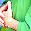 Hands clasped in prayer the priest — Stock Photo