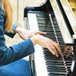 Stock Photo: Hands playing melody on piano