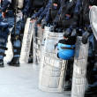 Постер, плакат: Policemen in riot gear with shields and helmets and helmets duri