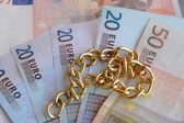 Necklace with money in euros in the background — Stock Photo
