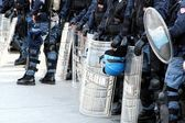 Policemen in riot gear with shields and helmets and helmets duri — Stock Photo