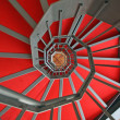 Iron spiral staircase with elegant red carpet and spiral — Stock Photo #22176775