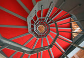 Iron spiral staircase with elegant red carpet and spiral — Stock Photo