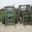 Two green tractors parked on a farm outdoors - 图库照片