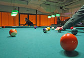Smoky poolroom with marbles on the carpet and attentive players — Stock Photo