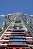 Pasos al cielo por un camión de bomberos con el autoscala en posición elevada — Foto de Stock