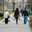 People with grocery bags for a walk in the City Park - Stock Photo
