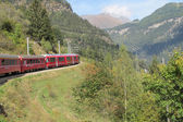 Red train around the beautiful Swiss mountains 16 — Stock Photo