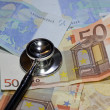 Stock Photo: Stethoscope doctor leaned on many sick euro currency banknotes