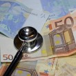 Stethoscope doctor leaned on many sick euro currency banknotes — Stock Photo