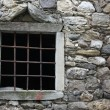Window with a metal grid on an old stone barn — Stock Photo