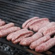 Sausage meat and steak in a barbecue in the garden — Stock Photo
