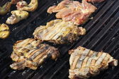 Thighs and chicken breasts cooked in a giant barbecue in the gar — Stock Photo
