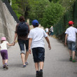 Family that runs along a narrow road uphill destroys — ストック写真