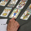 A reader's hand during the reading of the playing cards and Taro — Stock Photo