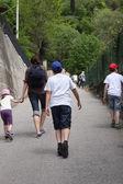 Family that runs along a narrow road uphill destroys — Stock Photo