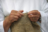 Hands of an elderly woman during the processing of wool sweater — Photo