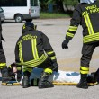 Постер, плакат: Firefighters carry a stretcher with serious injuries after the a