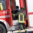 Stock Photo: Firefighters prepare for tools from truck during serio