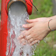 Wash hands under the powerful jet of water from a fire hydrant — Stock Photo #25248165