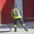 Firefighter in action during a fire with the water hose — Stock Photo #25248221