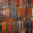 Many leather belts on sale at the local market in a stand - Stock Photo