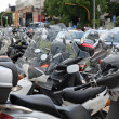 Many scooters and motorcycles parked in road car park - Stock Photo