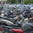 Many scooters and motorcycles parked in road car park — Stock Photo #25289309