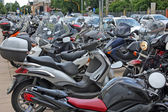 Many scooters and motorcycles parked in road car park — Stock Photo