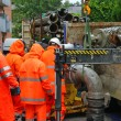Team of workers in rainwear works hard to install a pump road — 图库照片