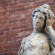 Stock Photo: Ancient statue with headaches and brick wall