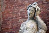 Ancient statue with headaches and the brick wall — Stock Photo