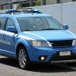 Blue Italipolice car whizzes quickly in middle of roa — Stock Photo #25933495