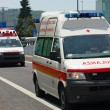 Two Italian Red Cross ambulance and a police car run fast in the — Stock Photo