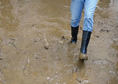 Black boots in the mud of the flood after natural disaster — Stock Photo
