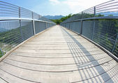 Bridge with a wooden walkway and handrail made of galvanized ste — Stock Photo