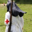 Red Cross nurse nun with big gun on her shoulders — Zdjęcie stockowe #27842997