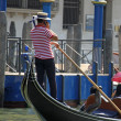 Skilled Venetian gondolier pilot his gondola while talking to ph — Stock Photo