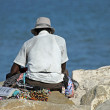 Stock Photo: Peddler of necklaces and accessories rests on Pier by se