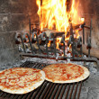 Excellent fragrant pizza baked in a wood fireplace with a wood-b — Stock Photo #29726841